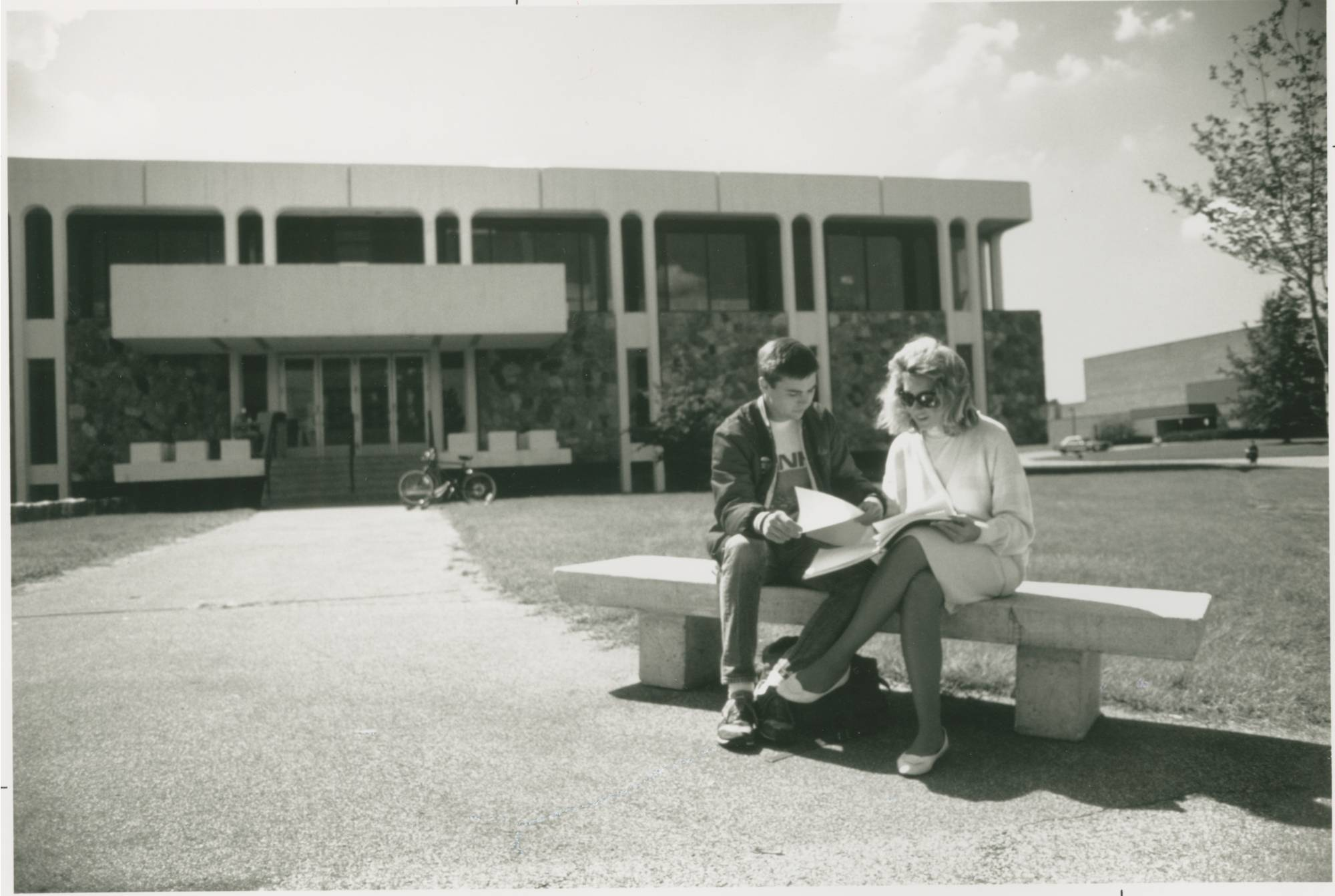A black and white photo of a couple sitting on a bench in front of Lake Superior Hall on a sunny day.